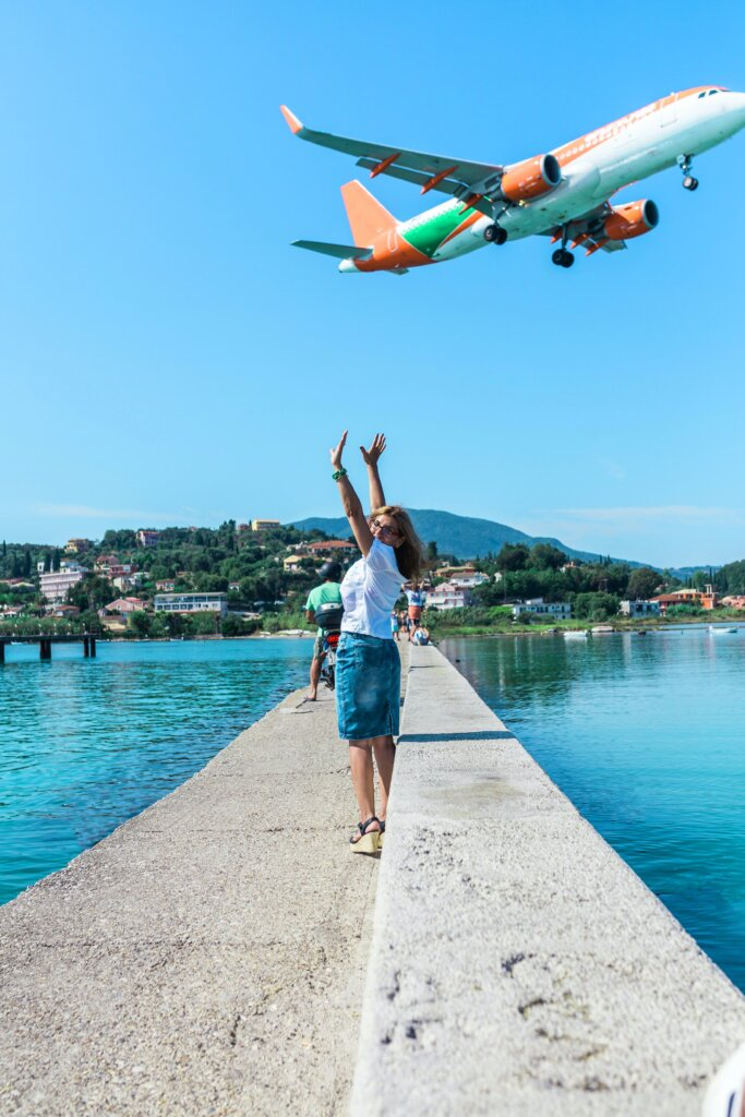 Woman on vacation waving at a plane in the sky
