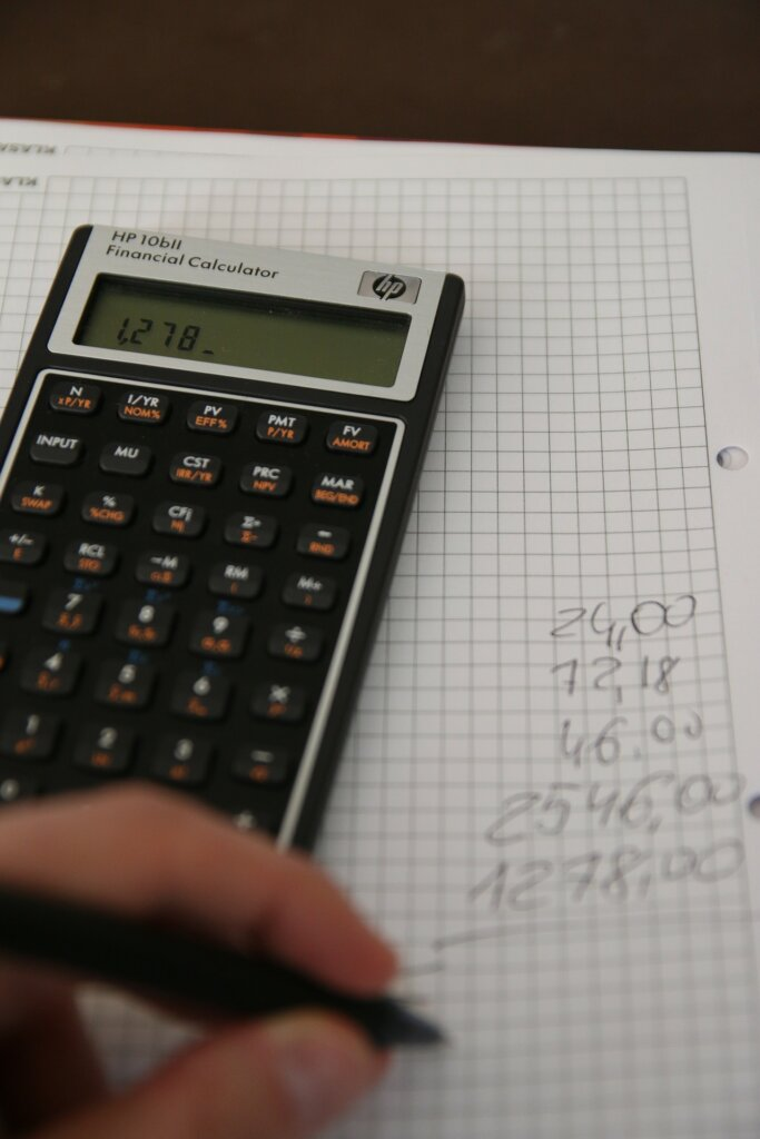 Person using a calculator on a grid notebook