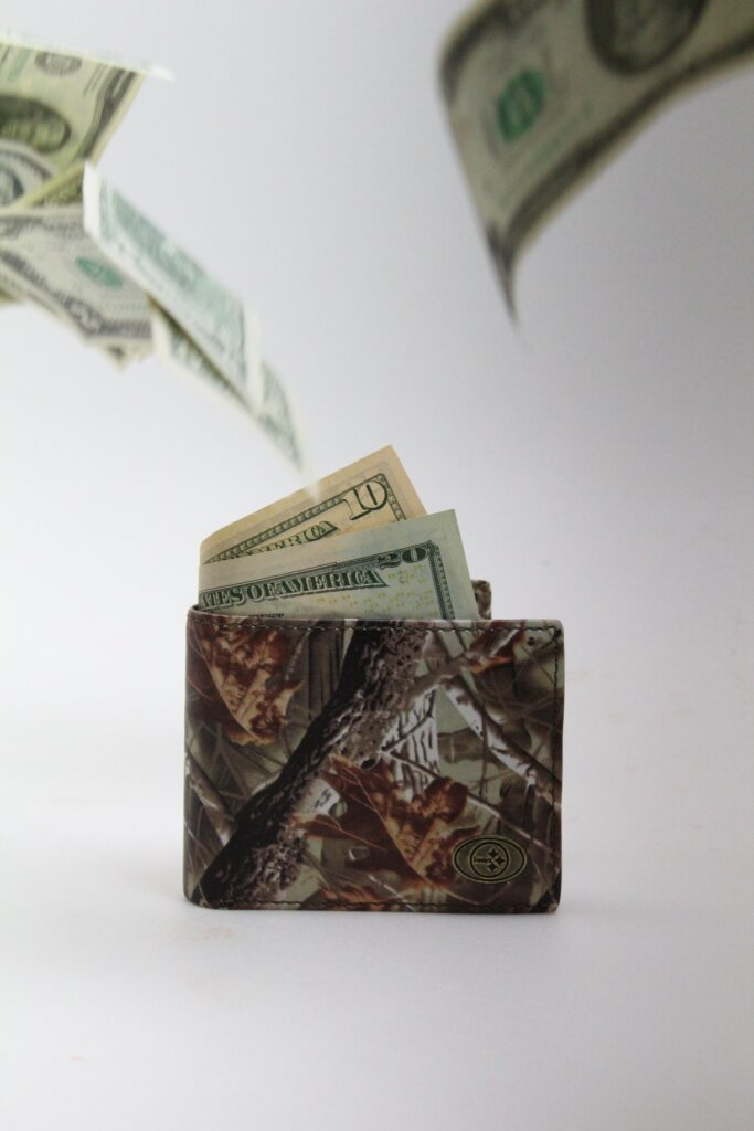 Dollar bills flying out of a wallet